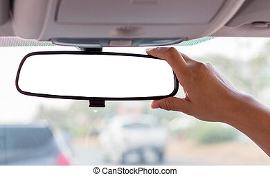 adjusting rear view mirror. - Hand adjusting rear view...