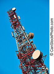 Telecommunication tower with antennas over blue sky.