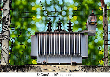 High voltage power transformer on green nature background