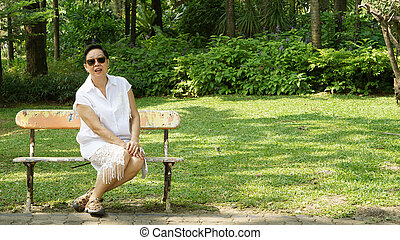 Asian senior woman sitting alone in bench park with copy space