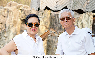 Asian senior couple have fun at zoo looking at african...