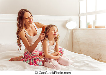 Mom with daughter - Beautiful young mother is combing her...