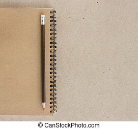 Small notepad with pencil and on wood background