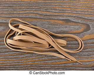 Brown shoe lace on the wooden background