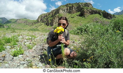 Girl collects wild flowers - Camera on steadicam moves to...
