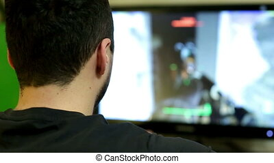 Young man playing a video game on personal computer at home