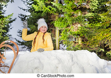 Happy girl throwing snowball from the snow tower in the...