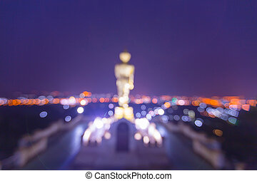 Blurred statue of buddha and city at Wat Phra That Kao Noi...