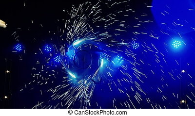 Wheel with pyrotechnics, silhouette artist with lights in...