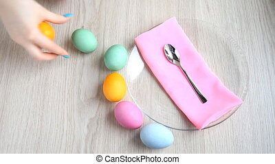 Lay out beautifully colored Easter eggs on the table - Hands...