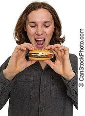 Young man eating a hamburger