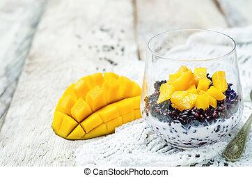 Coconut black rice mango pudding on white wood background....