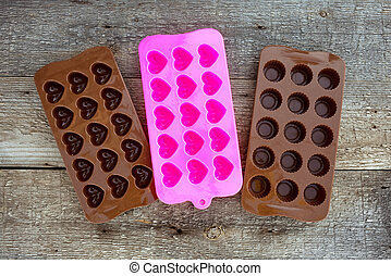 Silicone chocolate mold on wooden background.