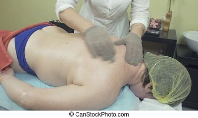 Masseuse make healing massage of back to fat woman by massage gloves in saloon.