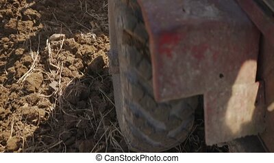 24-Tractor Moving In Field Closeup Of Tyre And Ground -...