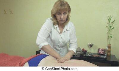 Masseuse make remedial massage of lower back, shoulder to...