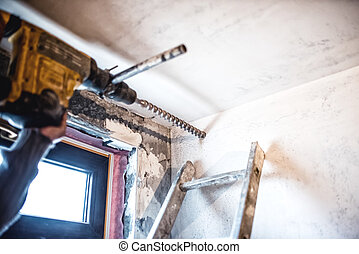 industrial worker drilling holes in walls using a...