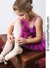 Ballerina dreamer - Young girl tying oversized pointe shoes...