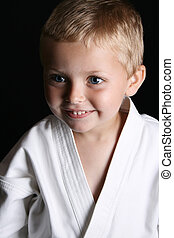 Karate Boy - Young boy wearing his karate uniform on a black...