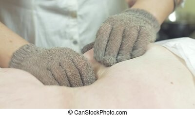 Masseuse make massage of fat stomach to woman in by massage gloves. Stroking