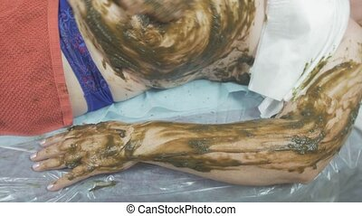 Cosmetologist put seaweed mixture on fat woman stomach, left hand. Spa wrapping