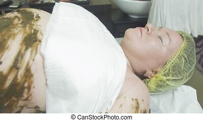 Adult fat woman lie with seaweed mixture on stomach, left hand. Spa wrapping