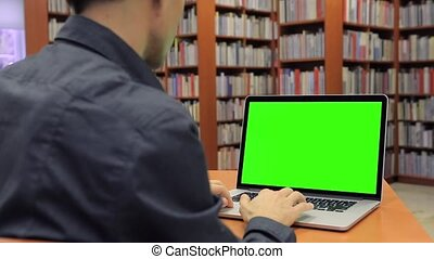 Young Handsome Man Sits and Works on Green Screen Laptop in the Library