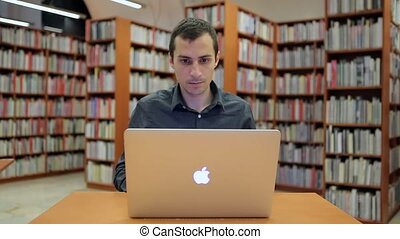 Young Handsome Man Sits and Works on MacBook
