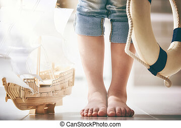dreams of sea, adventures and travel. - Child stands next to...
