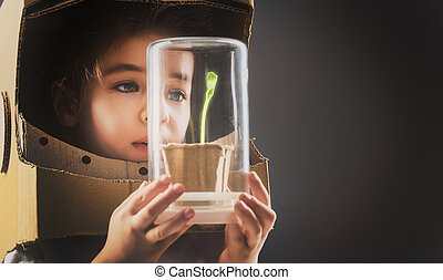 Child sees a sprout - Child is dressed in an astronaut...