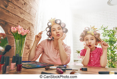 Happy loving family. Mother and daughter are doing hair,...