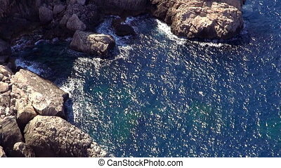Wonderful shot of deep blue ocean water at the cliffs on sunny day