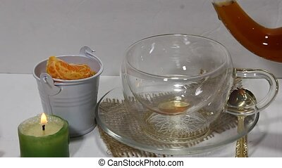 Pouring tea - A glass tea kettle pouring black tea in a...