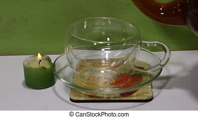 Pouring tea - A glass tea kettle pouring black tea in a...