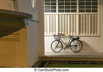 old bicycle close to the building wall in Singapore by night