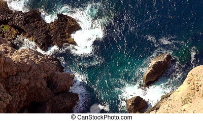 Aerial shot of the cliff line with deep blue water of the...