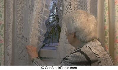 Elderly woman looking to window