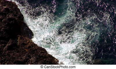 Breaking ocean waves at the cliffs aerial shot