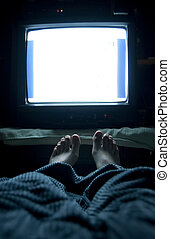TV In Bed - Person watches TV at night in his bed with his...