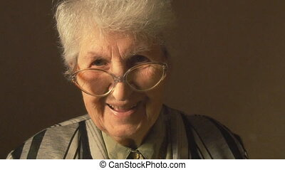 Old woman with eyeglasses looking at camera and smiling.