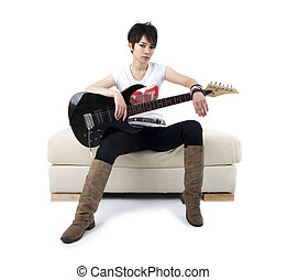 Punk Rockstar holding guitar sitting on sofa isolated in...
