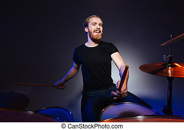 Attractive bearded man drummer playing drums with passion