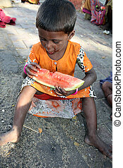 Hungry Poor Girl - A hungry beggar girl from India eating a...