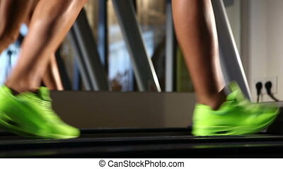 Beautiful woman's legs on treadmill - Exercising in the gym,...