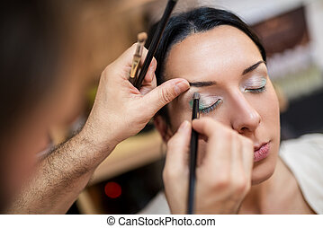 Make-up Artist - Make-up artist applying the eyeshadow to...