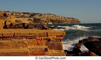 Rocky beach with turbulent water and breaking ocean waves