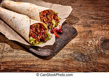 Pair of Chili Stuffed Tex Mex Wraps on Wood Table - Close Up...