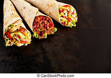 Trio of Tex Mex Fajita Wraps on Dark Counter - Close Up...