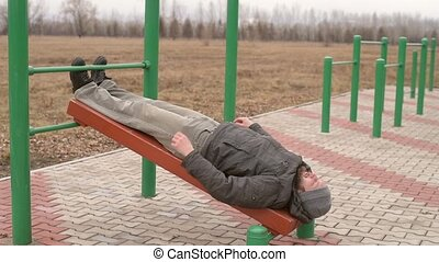 Man exercising abs in the park - Man exercising abs outdoors...