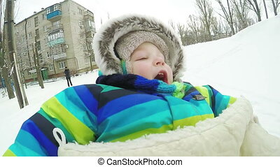 Child on sled in winter - Sitting on sleds yawn baby